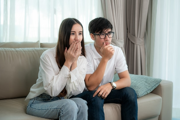 Asian couple man and woman watching and enjoying terror tv movie sitting on a couch together in the livingroom at home. family lifestyle relax and recreation concept.