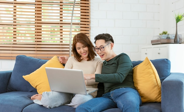 Asian couple man and woman watching movie in computer laptop together on sofa in living room at home. family lifestyle concept.