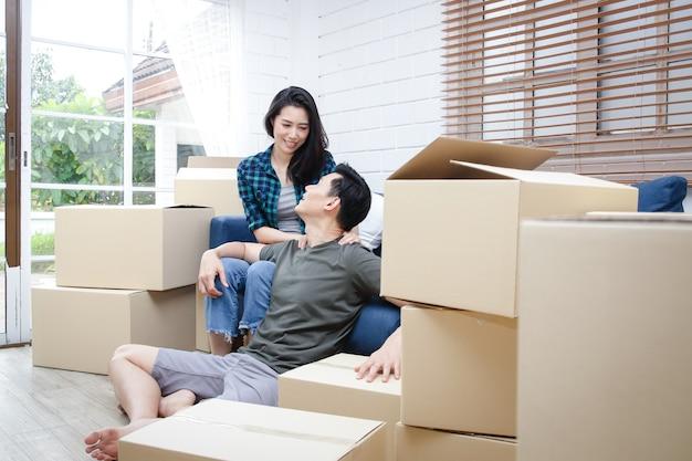 新しい家に引っ越すアジアのカップル家を飾るために茶色の紙箱を開梱するのを手伝ってください。新しい生活を始め、家族を築くというコンセプト。コピースペース