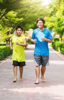 兄弟のアジア人のカップルが一緒に公園で走る。