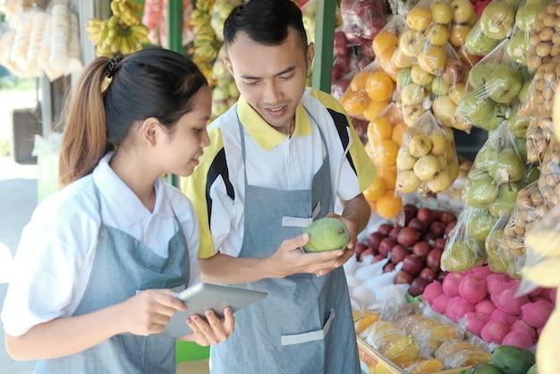 オンラインマーケティングのためのパッドを使用してアジアのカップルの所有者の新鮮な有機果物店