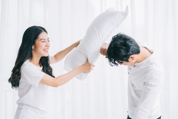 Asian couple playing together in the bedroom