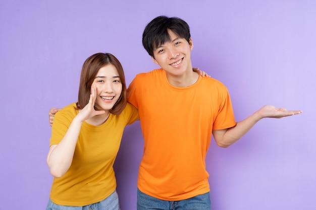 アジアのカップルの肖像画、紫色の背景に分離