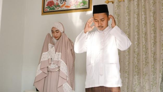 집에서 함께 기도하는 아시아 부부