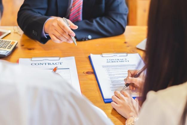 アジアのカップルは、会議での契約を読んで署名します。