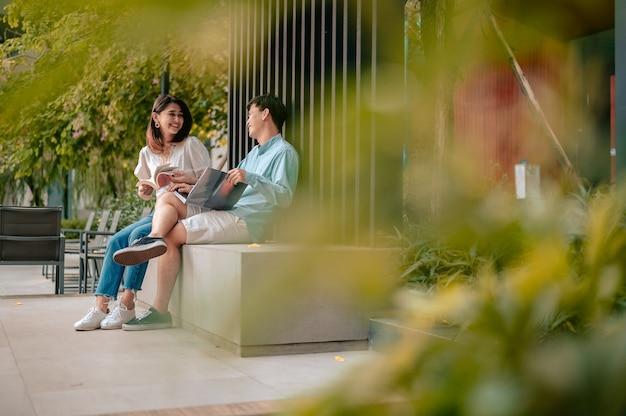 Азиатская пара, читающая книгу в парке в отеле. отпуск, влюбленная пара и концепция сладкой пары.