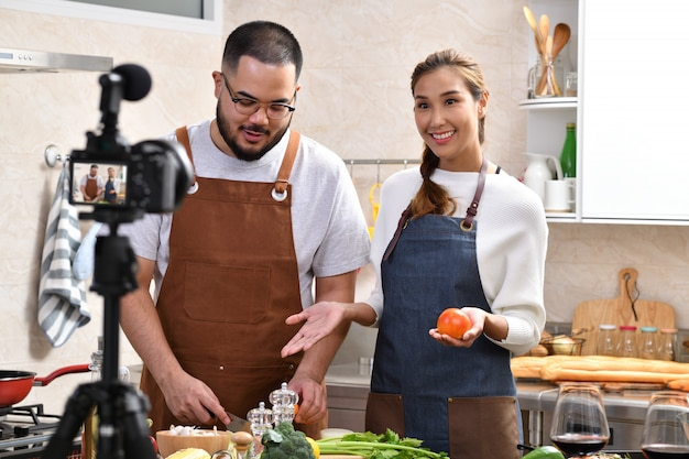 アジアのカップルが台所でビデオを録画