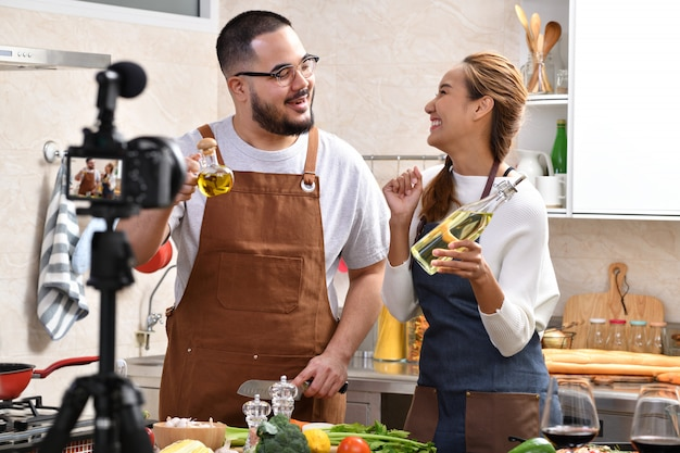 Asian couple recording a video in the kitchen