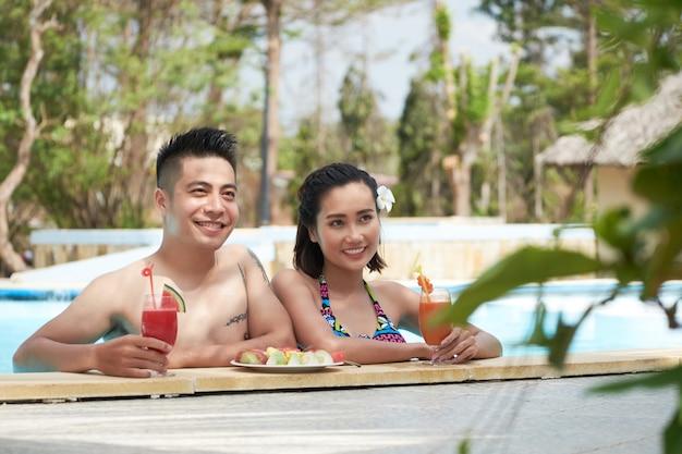 トロピカルリゾートで新鮮なジュースとスイミングプールでリラックスしたアジアカップル