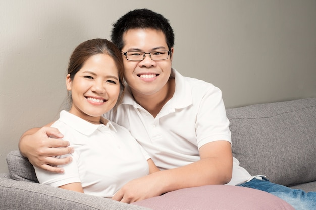 ソファでリラックスしたアジアのカップル