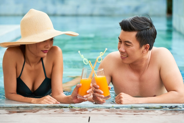 Asian couple resting in swimming pool