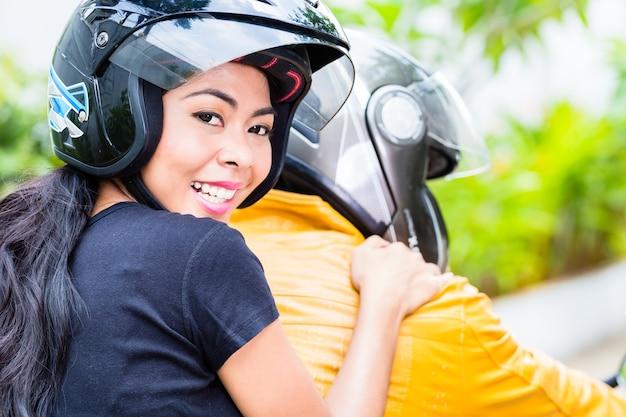 バイクに乗るアジアのカップル、妻は彼女の夫の後ろに座っています