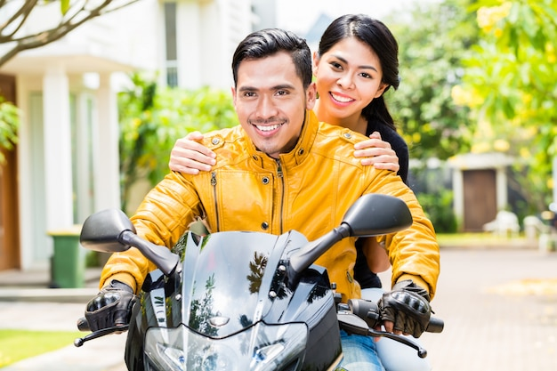 Asian couple riding motorcycle