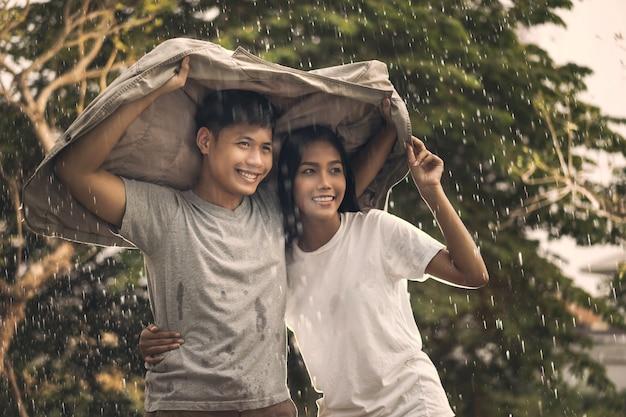 雨の中でアジア人カップルロマンチックな時間