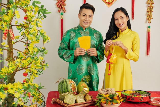 Asian couple in room decorated for tet