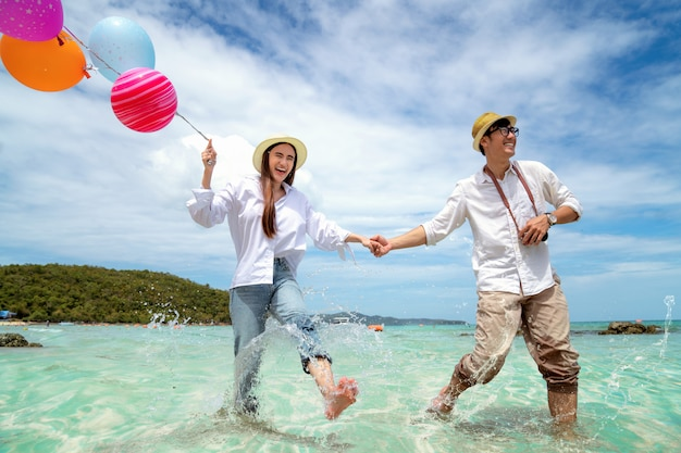 Asian couple run and happy on pattaya beach with balloon on hand