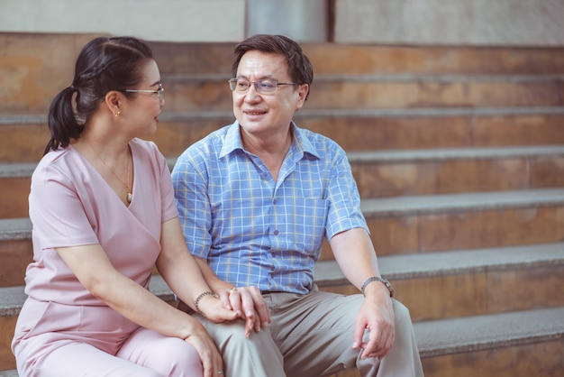 Asian couple senior man smiling look at senior woman hodling hands sitting on the stairs in city town while traveling