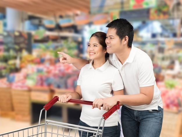 スーパーマーケットで買い物をするアジアのカップル