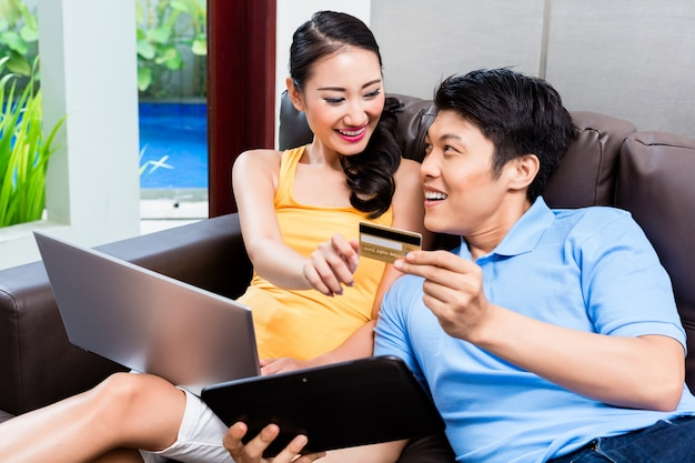 Asian couple shopping online in internet with laptop