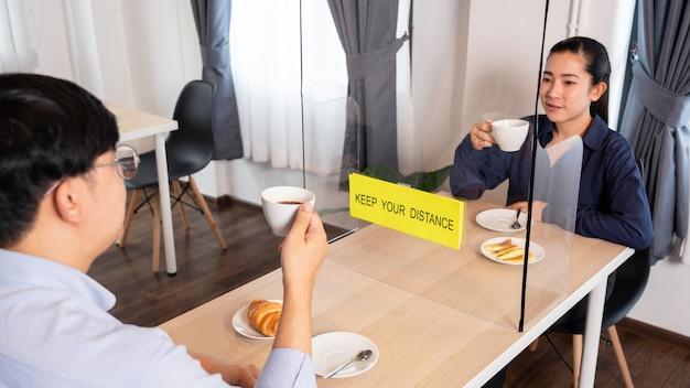 테이블 방패 플라스틱 파티션으로 음식을 먹는 레스토랑에서 분리 된 아시아 부부 앉아