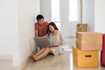 Asian couple sitting their new house and search for interior plan