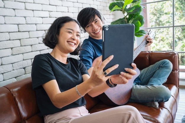 Азиатская пара улыбается с селфи и сидит на диване в гостиной