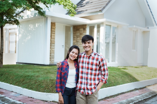 Asian couple standing in front of their new house