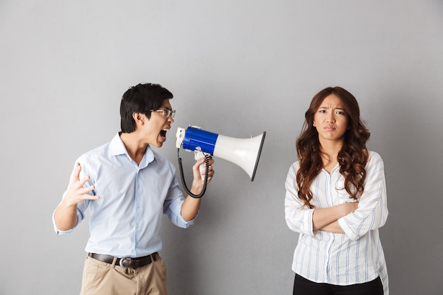 Asian couple standing, man yelling in a loudspeaker