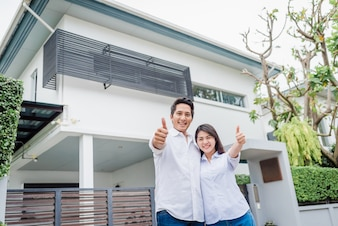 Asian couple standing together in front of thier house