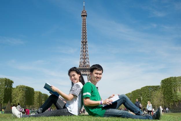 Азиатская книга чтения студента пар совместно на outdoors паркует около эйфелева башни в париже, франции.