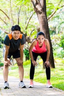 Asian couple take breathless break from running