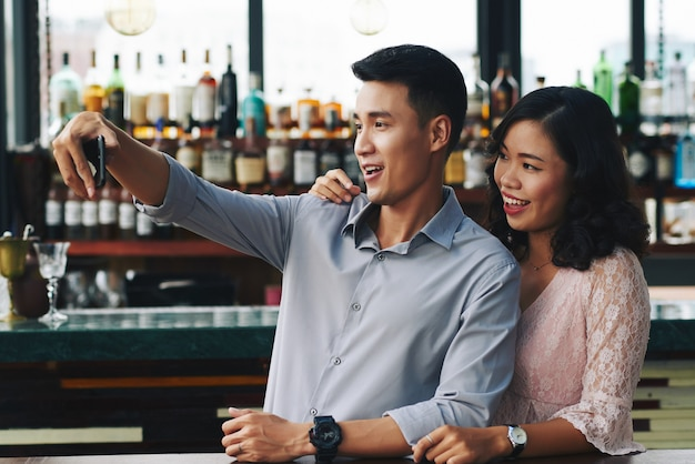Asian couple taking selfie on smartphone in bar