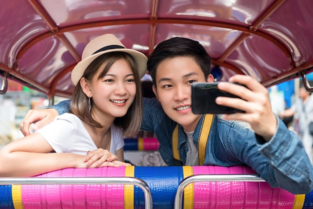 Asian couple taking selfie while traveling on local colorful tuk tuk taxi