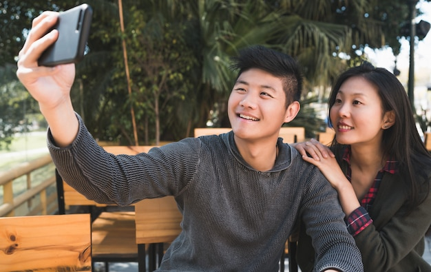 Asian couple taking a selfie with mobile phone.