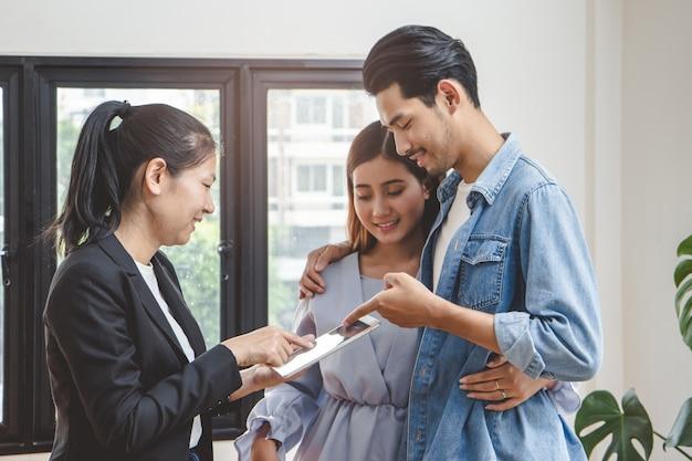 새 아파트를 사기 위해 부동산 소개업자와 이야기하는 아시아 부부