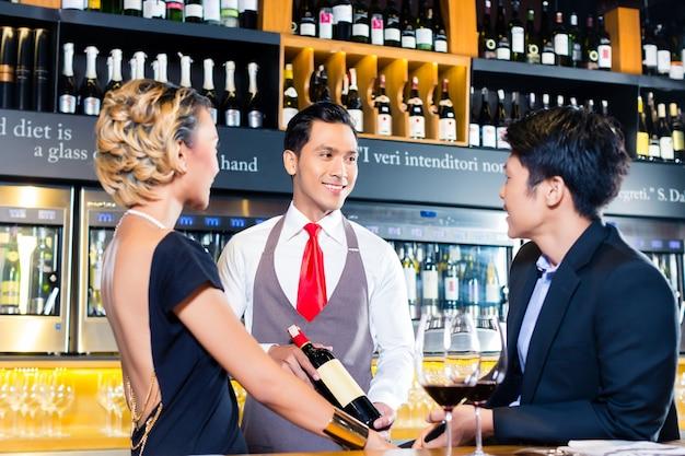ワインショップで赤ワインを味わうアジアのカップル