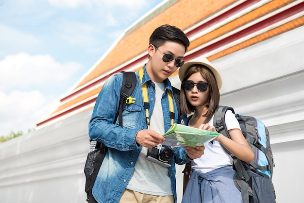 Asian couple tourist backpackers looking at the map beside temple wall while traveling on holidays