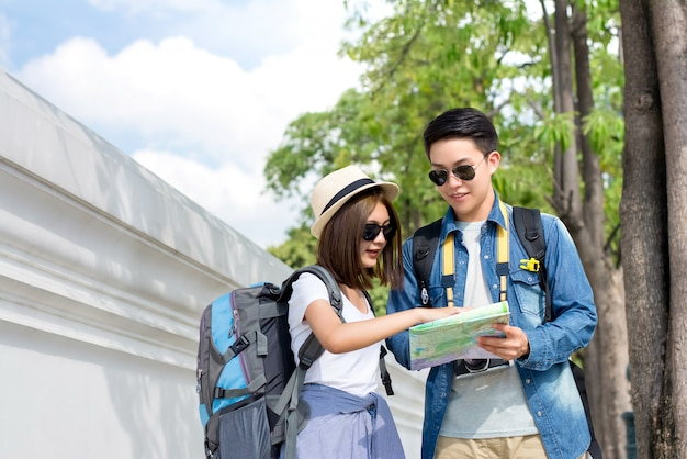 Asian couple tourist backpackers looking at the map while traveling in  thailand