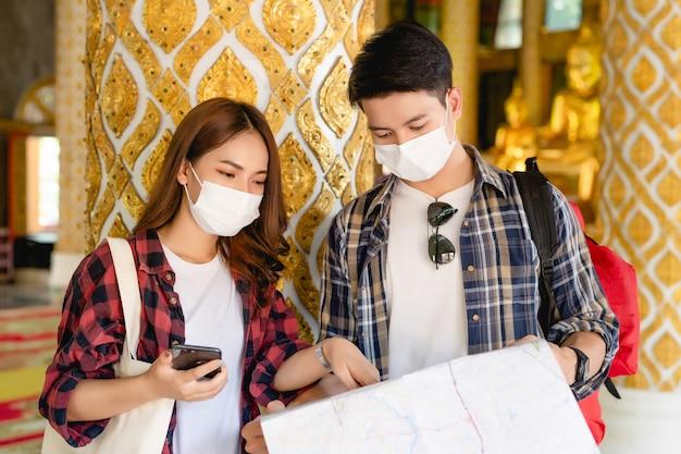 Coppia asiatica di turisti zaino in spalla in piedi nel bellissimo tempio tailandese, bella donna che tiene in mano uno smartphone e un bell'uomo che controlla la mappa cartacea durante il viaggio in vacanza