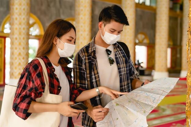 美しいタイの寺院に立っているアジアのカップルの観光バックパッカー、スマートフォンを持っているきれいな女性とハンサムな男性が休暇中の旅行中に紙の地図をチェックイン