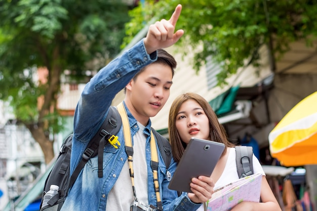 Asian couple tourist using tablet to find location while traveling in bangkok