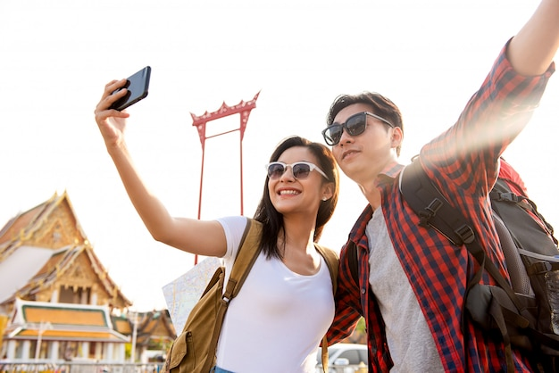 Asian couple tourists taking selfie while traveling in bangkok thailand