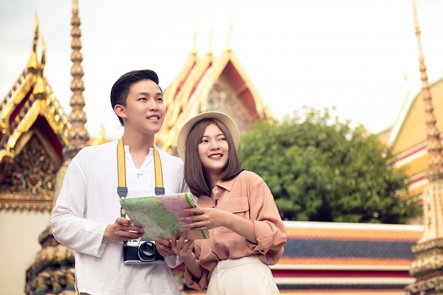 Asian couple tourists visiting thai temple, wat pho, in bangkok  thailand