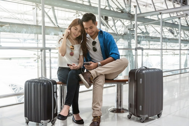Asian couple traveler using smartphone and listening the song