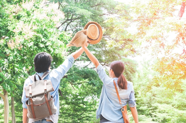 Asian couple traveling in green forest, happy travel