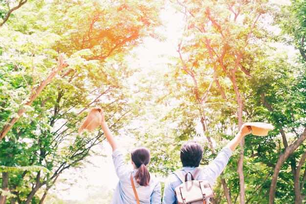 Asian couple traveling in the green forest, travel concept with sunlight