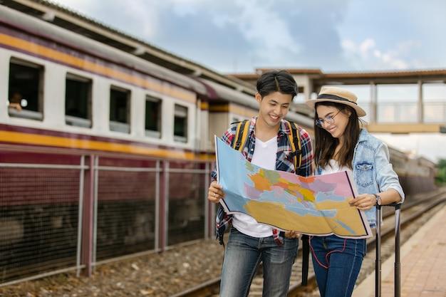 タイでは、列車の駅ヴィンテージスタイルの概念を旅行するアジア人のカップル