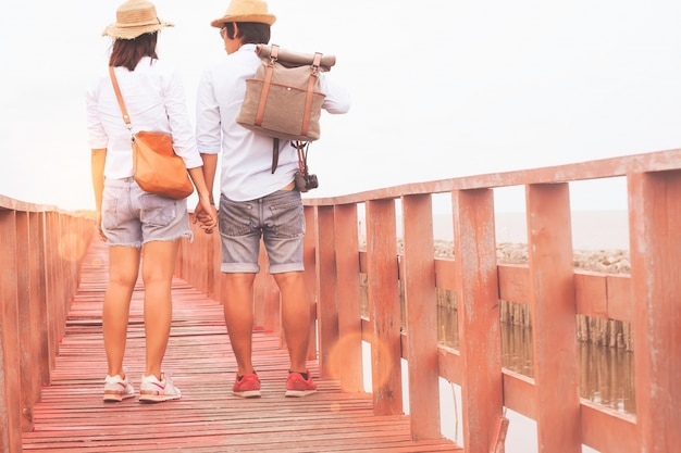 An asian couple traveller walking on wooden bridge seaside, love and travel concept