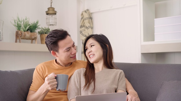 Asian couple using laptop and drinking warm cup of coffee in living room at home