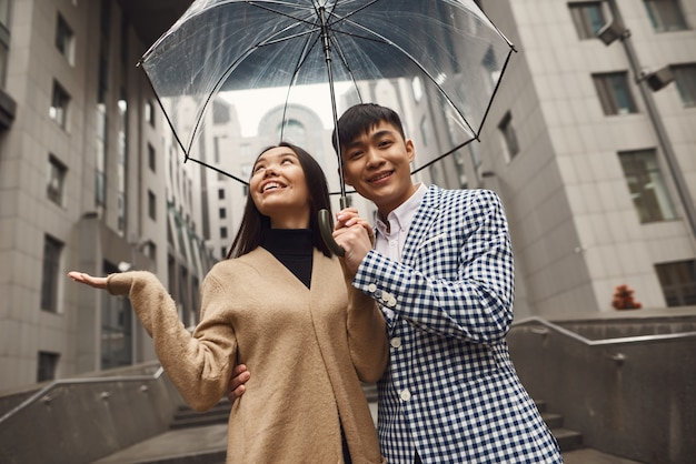 Asian couple walking together under umbrella.